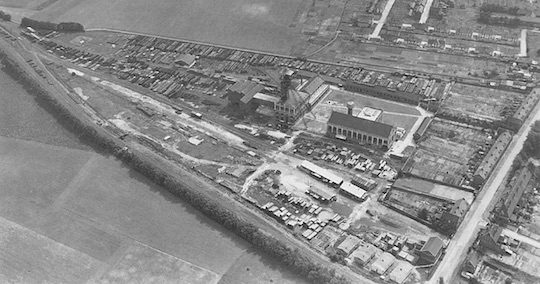 La chaufferie, aujourd'hui au coeur de la ville, a été installée sur le site de l'ancienne Fosse 14 de Lens, fermée en 1967 et à l'époque encore entourée de cultures