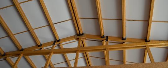 L'air réchauffé par le soleil entre le toit et le plafond du bâtiment sert à préchauffer l'air de chauffage des séchoirs, photo Frédéric Douard
