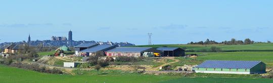 Vue de la ferme Chayriguès à Flavin, avec le hangar à plaquettes et son toit photovoltaïque à droite et en fond la cathédrale de Rodez, photo Frédéric Douard