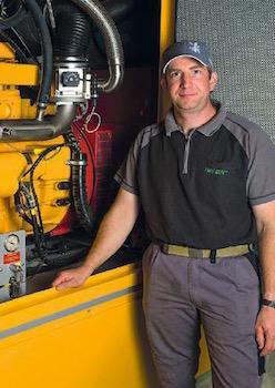 Simon Eschler, Agri Bio Val SA, devant la génératrice au biogaz, photo Aide Suisse aux Montagnards